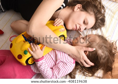 horizontal portrait of a young mother laying with her little daughter and car toy,looking at each other and smiling - stock photo