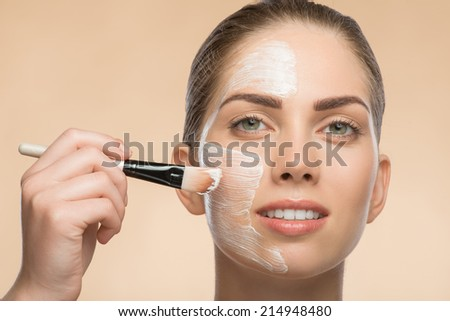 Horizontal Portrait of beautiful smiling girl in spa applying facial cosmetic cream with brush on her face isolated on beige background looking at the camera  with copy place - stock photo