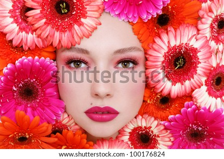Horizontal portrait of beautiful woman with stylish make-up and bright flowers around her face
