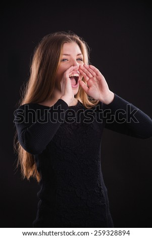 Horizontal portrait of beautiful young woman in black dress. Hand gesture on mouth