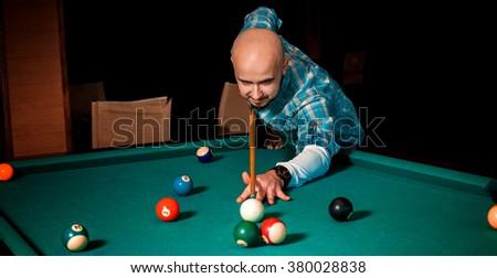 Horizontal portrait of concentrated man plays on billiard table. AMerican pool billiard. Pool billiard game. Billiard game concept. - stock photo