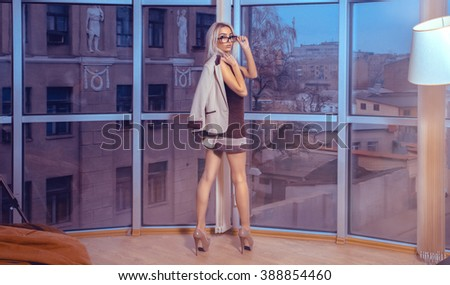 Horizontal portrait of fashionable young blonde lady posing by the large window with city views. Business woman posing. City views behind the window in the office. Business concept. - stock photo