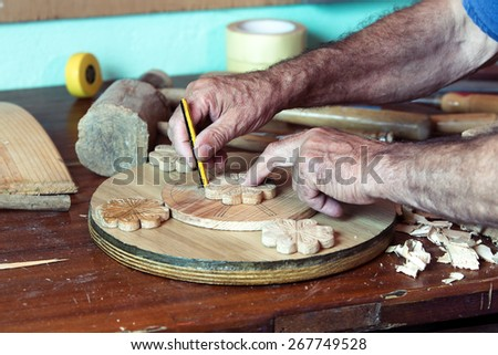 horizontal portrait of hands of carpenter marking with pencil handmade pieces of wood workshop / hands of cabinetmaker marking handcrafted wooden pieces in garage at home  - stock photo