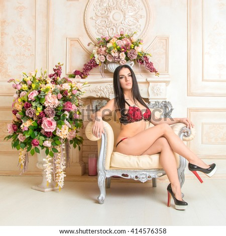 horizontal portrait of sexy young brunette woman posing in red lingerie on chair and looking at the camera - stock photo