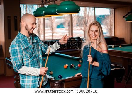 Horizontal portrait of smiling beautiful couple plays billiard. American pool billiard. Billiard sport concept. Pool billiard game. - stock photo