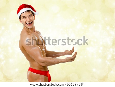 horizontal portrait very muscular  bronzed handsome sexy Santa Claus in red pants, smile - stock photo