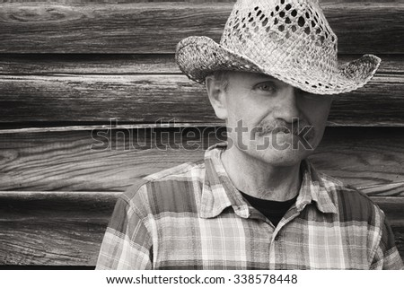 horizontal sepia head shot of a cowboy standing next to an old wood plank wall wearing a cowboy hat and checkered shirt with space for text. - stock photo