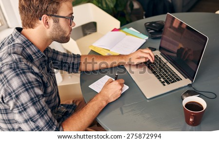 horizontal shot from above of a businessman busy taking notes from his notebook in the morning with his cup of coffee - stock photo