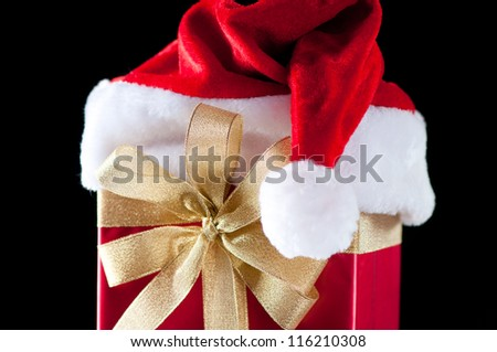 Horizontal shot of a gift box with Santa hat, black background