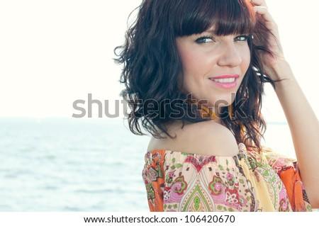 Horizontal shot of a sensual young woman standing near the shore - stock photo