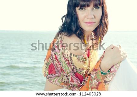 Horizontal shot of a young caucasian woman relaxing on the shore - stock photo