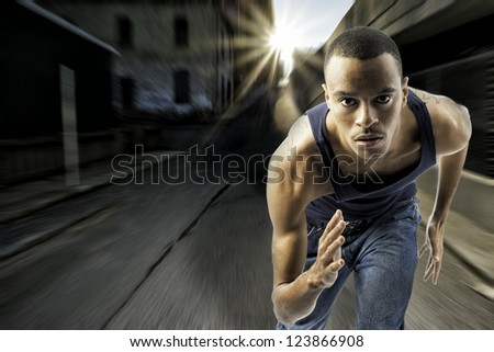 horizontal shot of black african american male running, urban setting with sun flare, motion blur, shows speed and determination, plenty of space for custom text