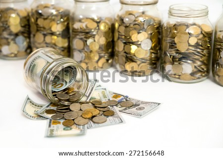 Horizontal shot of coins spilling from coin jar - stock photo