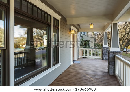 Horizontal Shot of wrap around porch on an upscale home/Large Porch Exterior of an Upscale Home