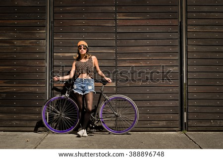 Horizontal shot of young latin woman with a bicycle standing over a wood fence. - stock photo