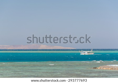 horizontal strip of sand, sea, sky and corals