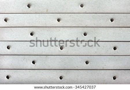 horizontal strips of old faded thick paper with holes