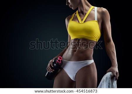 Horizontal studio shot of perfect abdomen muscles of a female athlete on black background with copyspace