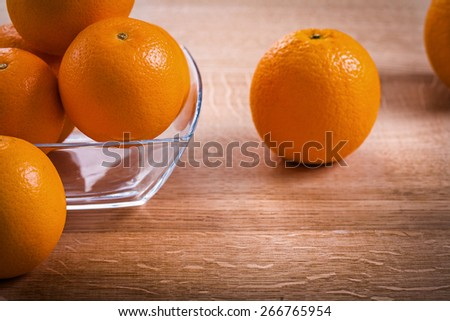 horizontal version orange fruits in glass square bowl on wooden board  - stock photo