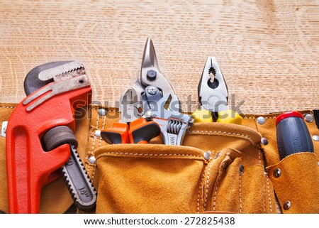 horizontal view construction tools in toolbelt monkey wrench nippers cutter pliers on wooden board  - stock photo