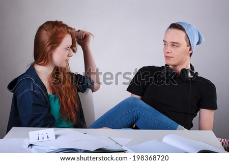 Horizontal view of a naughty teenagers talking in classroom - stock photo