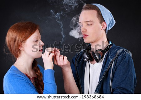 Horizontal view of a teenagers smoking marijuana joint  - stock photo