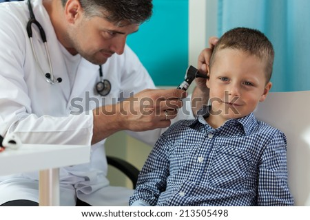 Horizontal view of boy during ear examination - stock photo