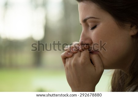 Horizontal view of depressed young woman crying - stock photo