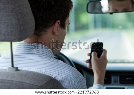 Horizontal view of driver using mobile phone - stock photo
