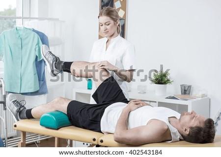 Horizontal view of female chiropractor exercising man's leg - stock photo