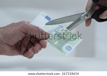 Horizontal view of hands cutting banknote