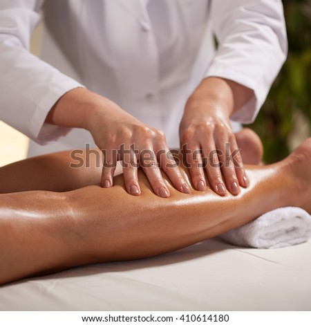Horizontal view of hands massaging female calf