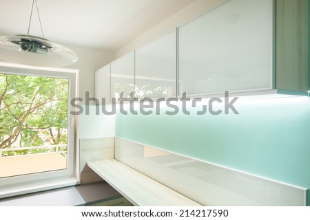 Horizontal view of kitchen with illuminated furniture - stock photo