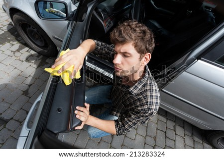 Horizontal view of man cleaning a car - stock photo