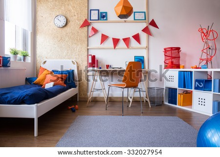 Horizontal view of modern teen boy bedroom - stock photo