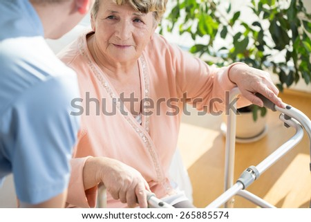 Horizontal view of nurse assisting disabled pensioner - stock photo