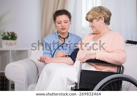 Horizontal view of nurse measuring blood pressure - stock photo