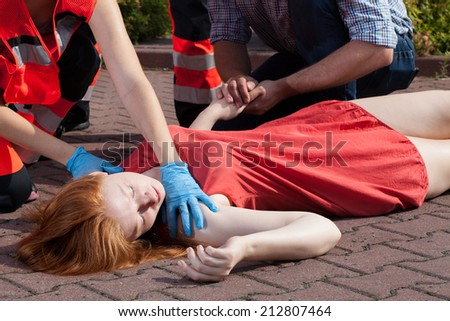 Horizontal view of paramedic helping unconscious woman - stock photo