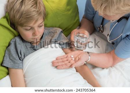 Horizontal view of physician giving boy medicine - stock photo