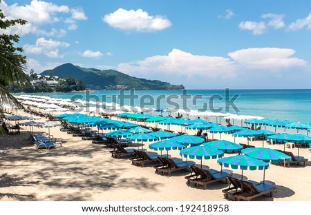 Horizontal view of several white and blue parasols and sun beds on a beach with a view of the ocean, blue sky and hills beyond. - stock photo