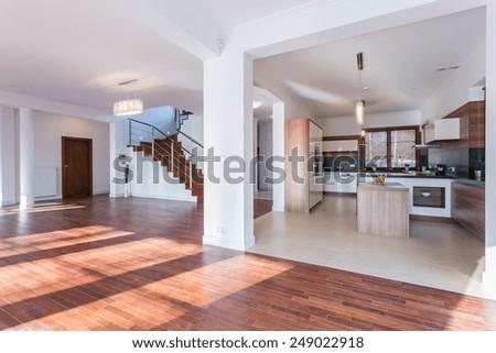 Horizontal view of spacious hall and open kitchen - stock photo