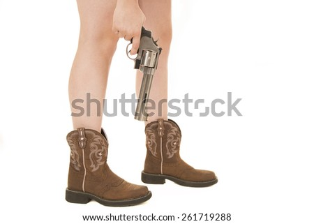 Horizontal woman's legs in boots with gun - stock photo