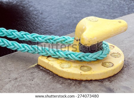 Horizontally oriented picture of port pier with yellow mooring bollard and green ropes - stock photo