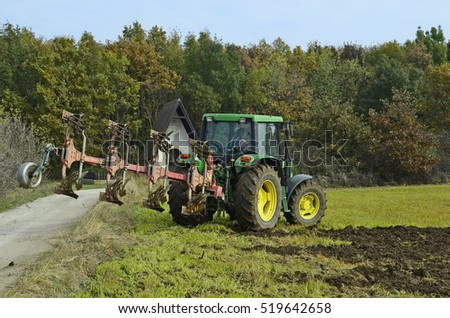 HORNSTEIN, BURGENLAND; AUSTRIA - OCTOBER 28: Unidentified farmer plowing field with tractor, small chapel at forest edge, on October 28, 2016 in Hornstein, Austria
