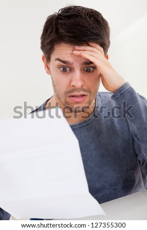 Horrified young man reading a document with an aghast expression and his hand to his forehead as he stares wide eyed at the page of paper - stock photo