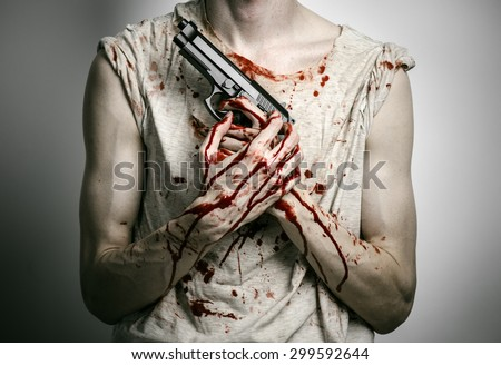 Horror and firearms topic: the bloody killer with a gun on a gray background in the studio - stock photo