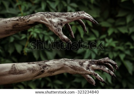 Horror and Halloween theme: Terrible zombie hands dirty with black nails reaches for green leaves, walking dead apocalypse - stock photo