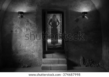 Horror girl dressed in black appears in a dungeon - stock photo