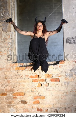 Horror Scene of a Scary Female Ghost at the Window. Capricorn or Goat woman. - stock photo