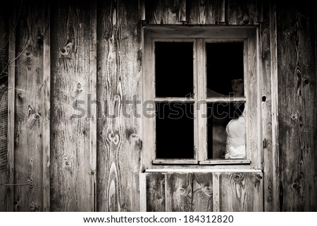 Horror scene of a scary woman. Mysterious woman staring out the window. - stock photo